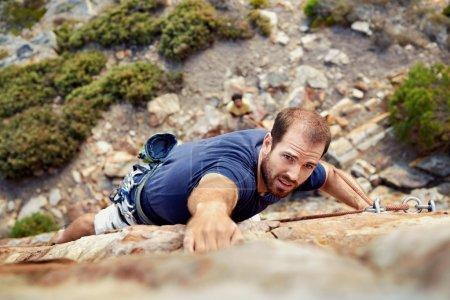 man rock climbs on steep cliff
