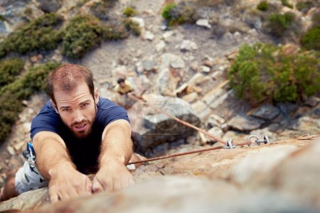 Photo for A man holding on to a piece of rock while he climbs up a steep cliff with copyspace - Royalty Free Image