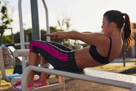 Woman doing situps in outdoor gym
