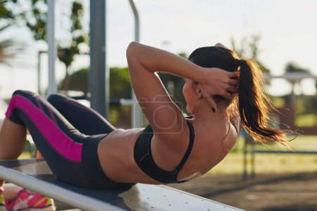 Photo for Fitness woman doing situps in outdoor gym woking out strength training - Royalty Free Image