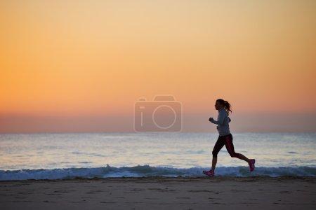 Woman running on beach in morning
