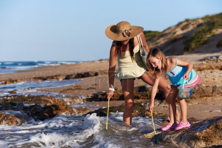Mother and daughter fishing at beach