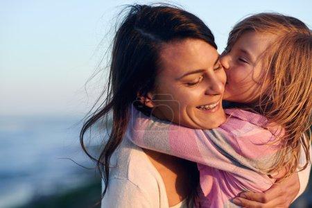 Photo pour Amour inconditionnel entre mère et fille étreindre et embrasser avec un baiser et un câlin à l'extérieur s'amuser - image libre de droit
