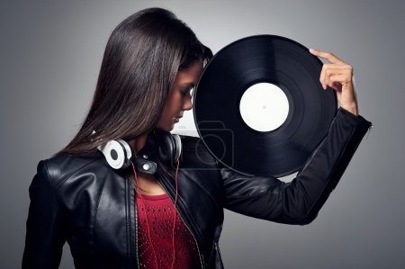 Woman dj with vinyl record and headphones