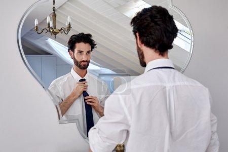 Photo for Professional man getting ready morning routine shirt and tie in bathroom at home - Royalty Free Image