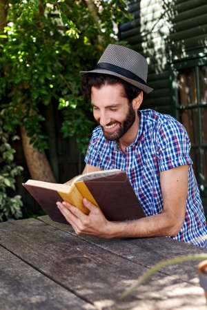 man outdoors reading book at home