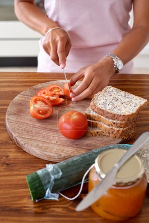 Photo for Woman making tomato and cucumber sandwich kitchen at home - Royalty Free Image