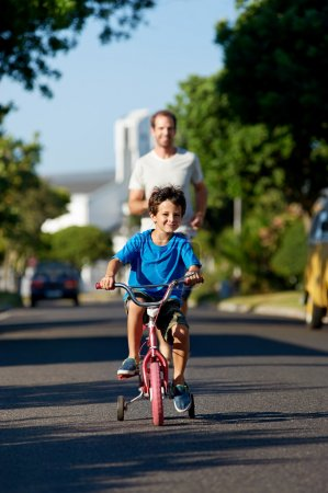 Photo for Father teaching son learning to ride bicycle boy - Royalty Free Image