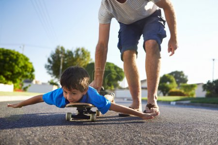 boy learning to ride skateboard