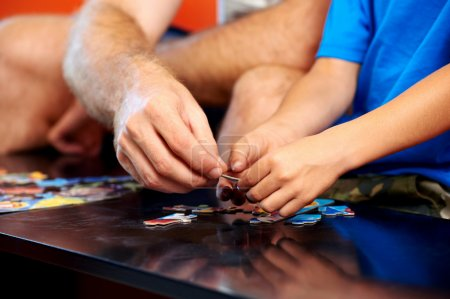Father and son hands holding puzzle