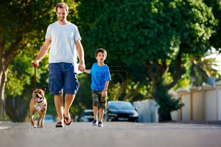 Photo for A father walking with his dog and his son in the suburbs - Royalty Free Image