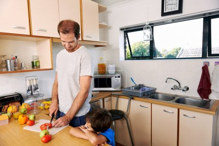 boy watching father prepare lunch