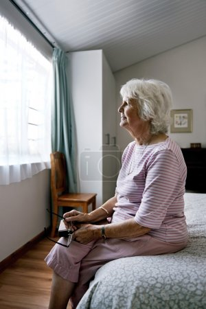 senior widow on bed feeling sad
