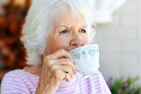 Photo for A senior woman taking a sip of her tea - Royalty Free Image