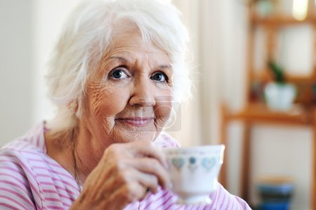 Old lady holding cup of tea