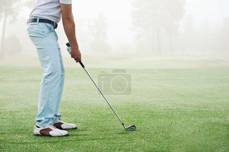 Golfer hitting golf shot with club