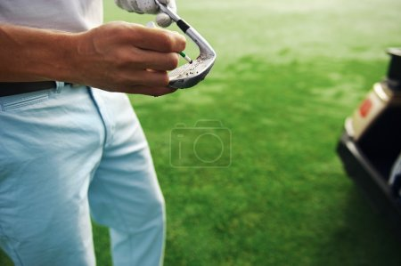 Golfer removes dirt and sand from grooves