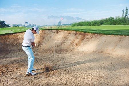 Golf shot from sand bunker golfer hitting ball fro...