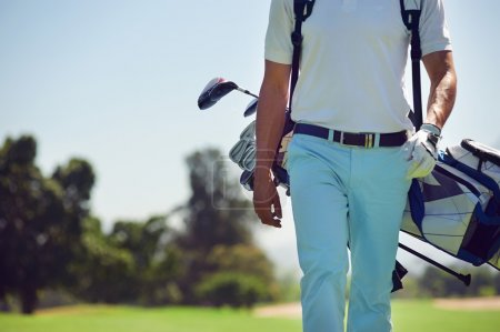 Golf player walking and carrying bag