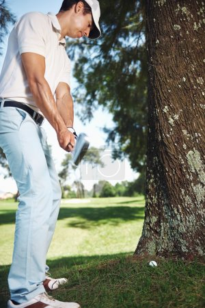 Golfer in difficult situation behind tree