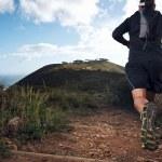 Trail running man on mountain path exercising...