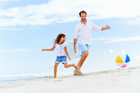 Photo for Happy healthy family father and daughter running on the beach with ball having fun together - Royalty Free Image