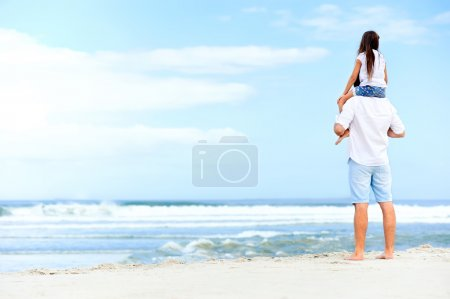 father with daughter walking on beach