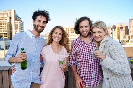 Foto de Potrait de feliz grupo de amigos que se divierten con bebida en la terraza de la azotea al aire libre - Imagen libre de derechos