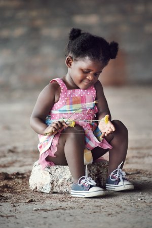 African child sitting on rock
