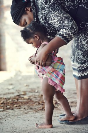 African mother teaching baby to walk