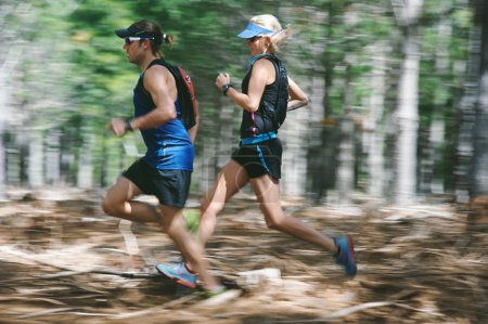 Couple running fast through forest