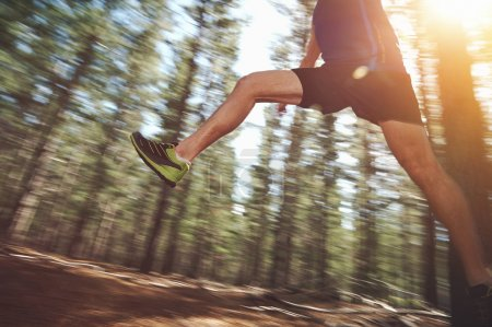 Runner jumping on trail run in forest