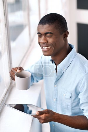 african man with coffee and tablet