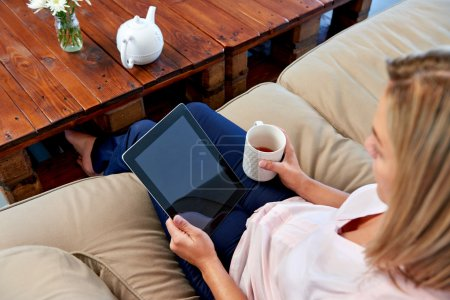 Woman on sofa reading email on tablet