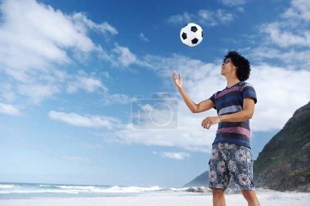 Man with soccer ball on beach