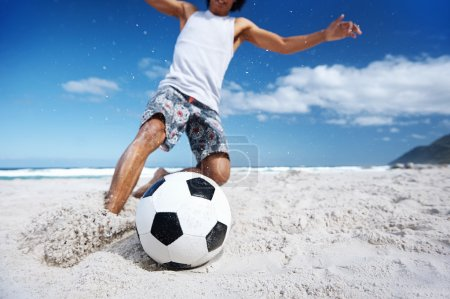 Brasil man playing soccer on beach