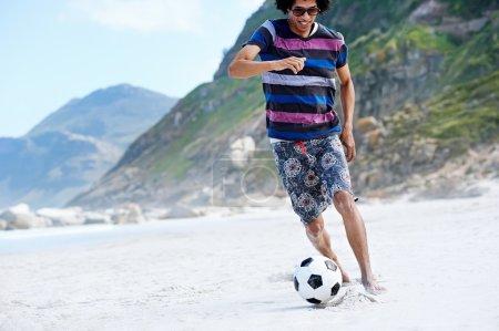 Brasil man playing soccer on beach