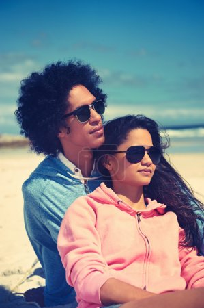 Latino couple sitting on beach