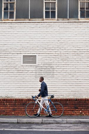 african man with bicycle walking