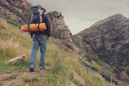 man hiking wilderness mountain with backpack