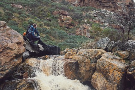 Photo pour Homme d'aventure traversant la rivière sur la randonnée extrême dans les montagnes seulement - image libre de droit