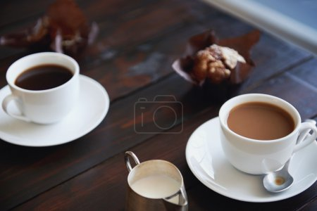 Cups of plain coffee with muffins