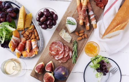 Photo for Cheese and cured meat charcuterie selection salami, chorizo, prosciutto wrapped bread sticks with fresh fig, rockmelon, almonds and white wine - Royalty Free Image