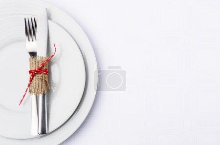 einfache Tischdekoration mit Klett und Band auf weißen Tellern