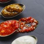 Variety of condiments on vintage spoons on slate b...