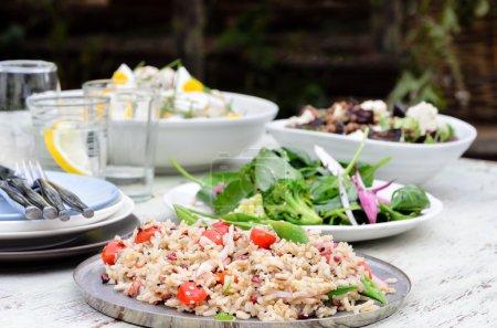 Photo pour Style de jardin été divertissant, buffet avec différentes salades sur la table, le vert feuillu, le pilaf de riz aux tomates cerises - image libre de droit