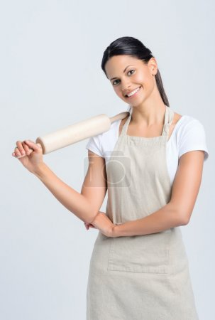Photo for Happy baker chef in apron holding a rolling pin - Royalty Free Image