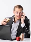 Multi tasking businessman eats and works