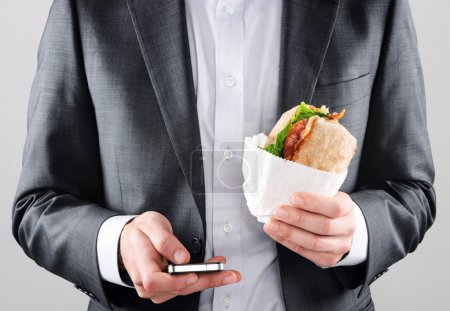 Man in suit sending sms while getting lunch