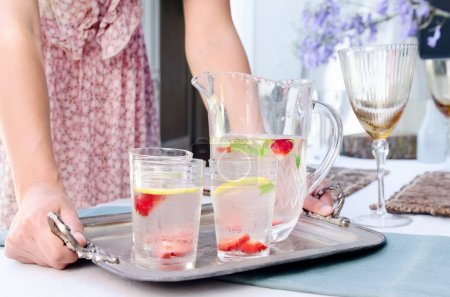 Party planner bringing water to the table